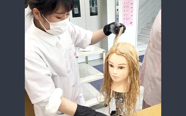マネキンでヘアカラーの練習する学生