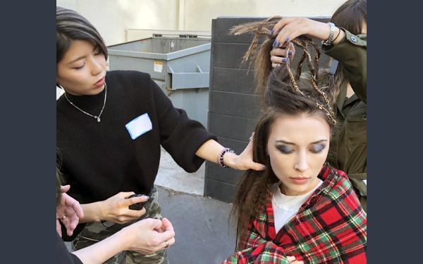 モデルのヘアセットをおこなう学生たち